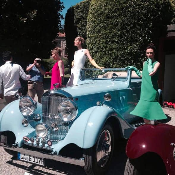 a fashion photo with models standing by a beautiful old car