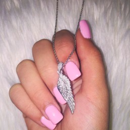 A hand with pink nail polish holding a silver necklace