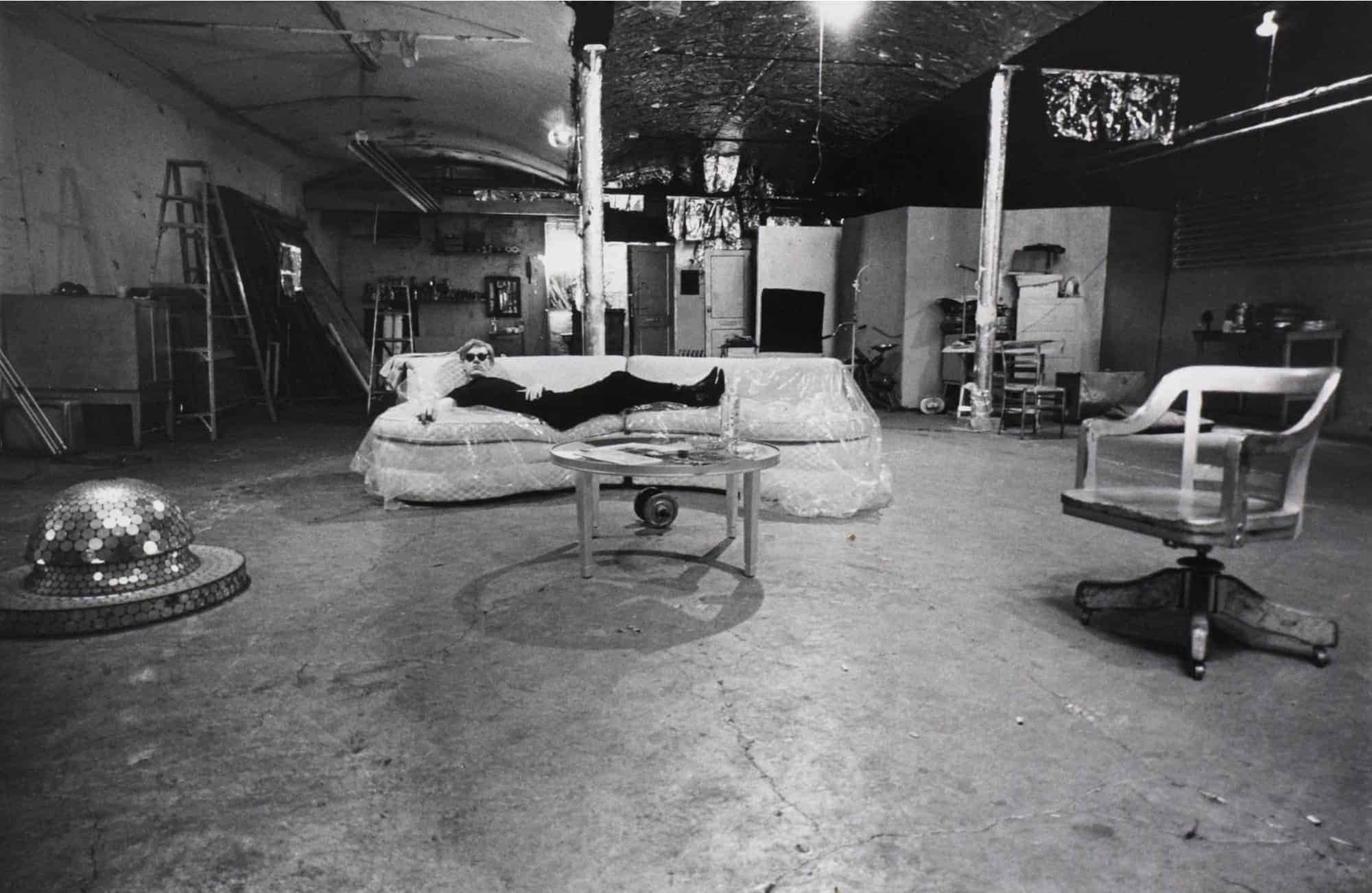 Andy Warhol on a couch at the Factory