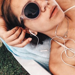Alla lying down wearing sunglasses and listening to music