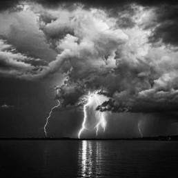 black and white photo of sky and water at night during a lightning strike